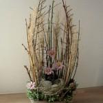 dekoration med grene,rede af græs, æg og keramikblomster